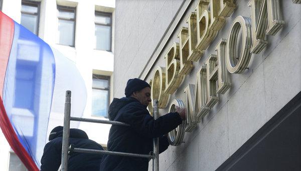 Рабочие устанавливают надпись Верховный Совет вместо демонтированной вывески с названием Верховная Рада на здание парламента Крыма