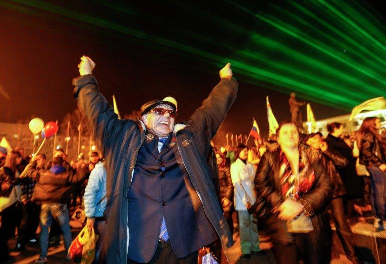 Люди наблюдают за праздничным салютом в честь присоединения Крыма к Российской Федерации на главной площади Симферополя