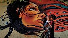 Мама с ребенком проходит мимо граффити в Мумбаи