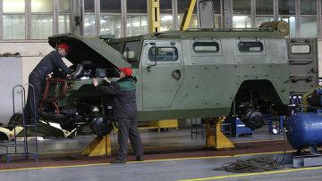 Рабочие осматривают военный бронеавтомобиль Тигр. Архивное фото