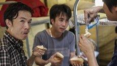 Вьетнамские мигранты обедают во временном лагере в Гольяново