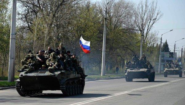 Люди, одетые в военную форму на боевой технике с флагом России около Краматорска