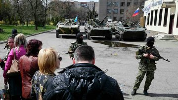Местные жители стоят возле вооруженных людей, охраняющих БТР в Славянске