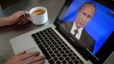 Жительница Новосибирска смотрит трансляцию ежегодной программы Прямая линия с Владимиром Путиным на экране ноутбука