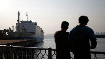 Люди смотрят на паром компании Chonghaejin Marine Co., которой принадлежал затонувший у берегов Южной Кореи паром Севол