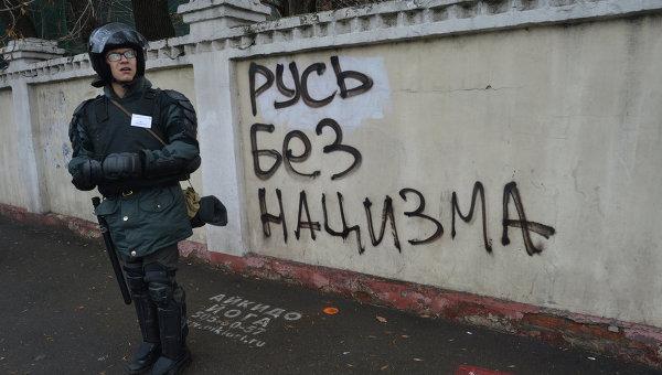 Сотрудник правоохранительных органов стоит в усилении во время проведения Русского марша в Москве.