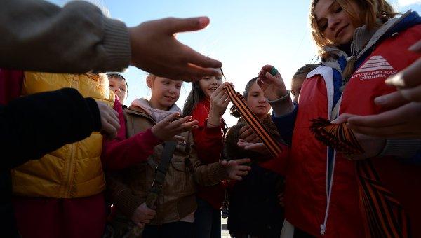 Волонтер раздает георгиевские ленточки детям на Поклонной горе в Москве. Архивное фото