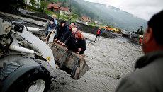Люди переносятся фронтальным погрузчиком, во время эвакуации недалеко от города Жепче