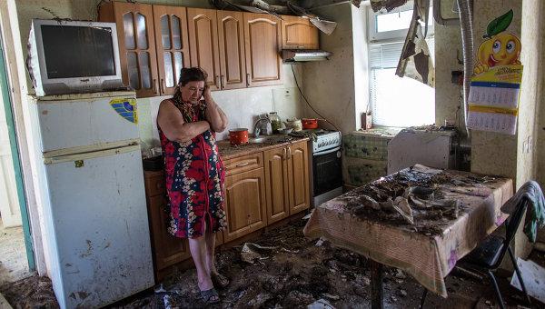 Женщина в своем доме, разрушенном в результате ночного артобстрела со стороны украинских военных на окраине Славянска