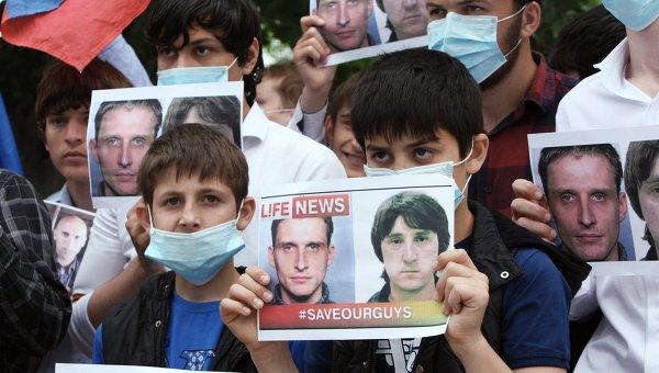 Активисты держат фото Олега Сидякина и Марата Сайченко во время акции в поддержку задержанных на Украине российских журналистов