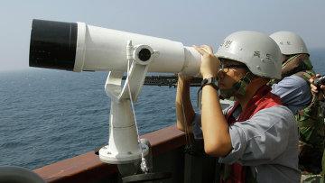 Офицер ВМФ Южной Кореи наблюдает в бинокль