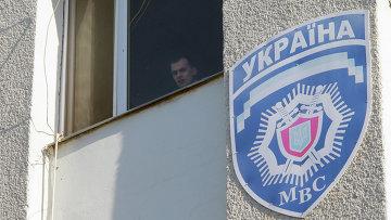 Милиционер смотрит из окна здания областного управления МВД Украины. Архивное фото