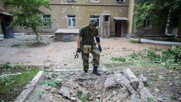 Боец народного ополчения у воронки от снаряда во дворе больницы в поселке Семеновка. Архивное фото