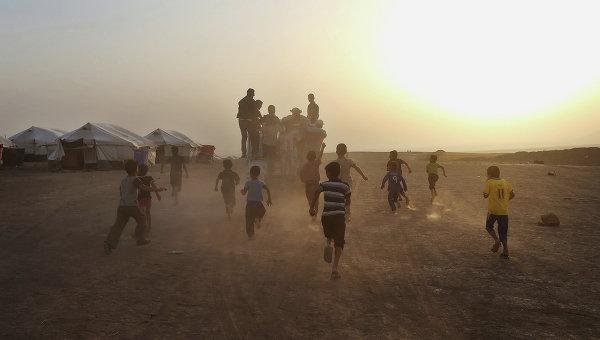 Дети бегут за грузовиком в лагере для беженцев на севере Ирака. Архивное фото.