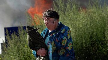 Женщина плачет возле своего горящего дома в Славянске. Архивное фото