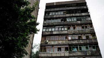 Окна с выбитыми стеклами в результате минометного обстрела украинскими силовиками в жилом многоквартирном доме в Луганске. Архивное фото