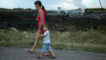 Женщина с ребенком проходят мимо места крушения крушения самолета Боинг 777 в Донецкой области
