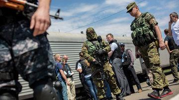 Сотрудники миссии ОБСЕ на станции города Торез перед отправкой в Донецк поезда с пятью рефрижераторными вагонами с телами погибших в авиакатастрофе малайзийского Boeing 777