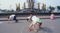 Дети рисуют мелом на асфальте у фонтана Дружба народов