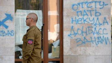 Ополченец у здания Областной городской администрации в Донецке