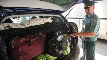 Сотрудник таможенного поста досматривает содержимое легкового автомобиля