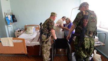 Ополченцы помогают пациенту в городской больнице Горловки