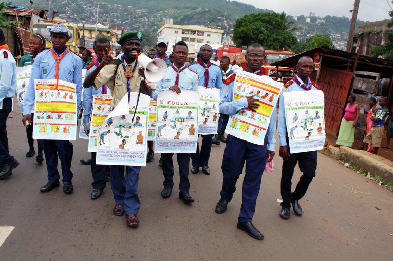 Члены ЮНИСЕФ несут плакаты с описанием симптомов заражения вирусом эбола