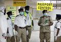 Сотрудники службы охраны здоровья ждут прибытия пассажиров в аэропорту Нигерии