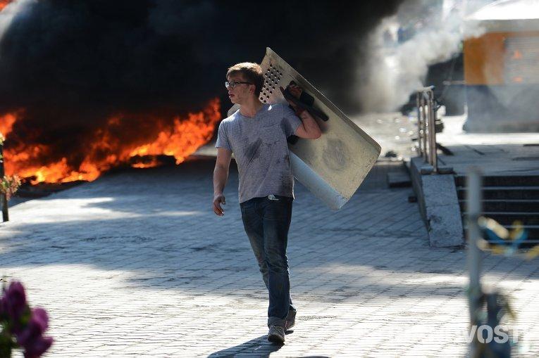 Активист идет мимо подожженных покрышек на площади Независимости в Киеве