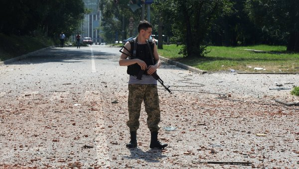 Ополченец около жилого дома в центре Донецка, пострадавшего при артиллерийском обстреле города украинской армией. Архивное фото