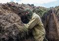 Ополченец в траншее на передовой позиции в поселке Семеновка.