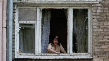 Женщина в окне квартиры после обстрела украинскими военными Донецка