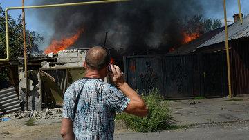 Мужчина у горящего дома в Петровском районе Донецка. Архивное фото