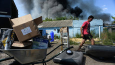 Местный житель выносит вещи из горящего дома в Петровском районе Донецка