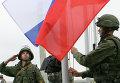 Солдаты поднимают российский флаг в полевом лагере