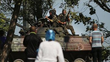 Местные жители наблюдают за украинским танком на окраине Мариуполя