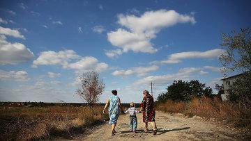 Девочка, ее мама и бабушка идут по разбитой дороге на окраине Луганска