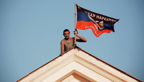 Ополченец Донецкой народной республики (ДНР) устанавливает флаг ДНР на здании мэрии города Комсомольское Донецкой области. Архивное фото