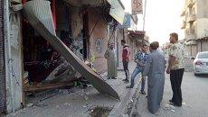 Жители города Ракка осматривают разрушенный магазин после падения беспилотника