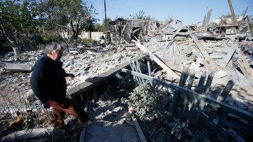 Женщина возле руин дома подвергшегося обстрелу украинскими военными