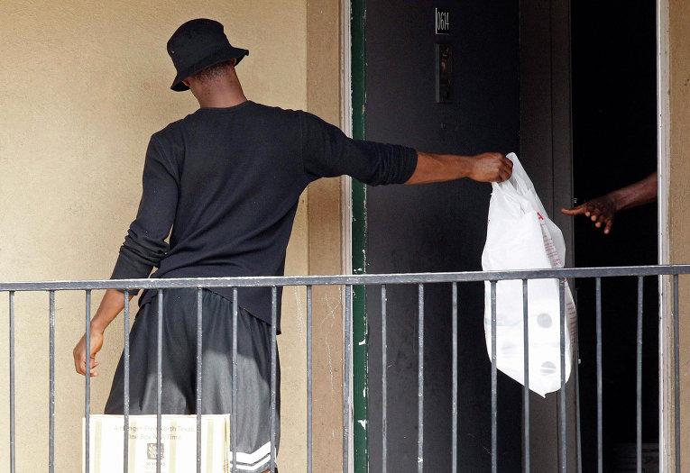 Работник из организации Красный крест доставляет вещи в аппартаменты заболевшего лихорадкой Эбола жителя в Далласе, Техас. 3 октября 2014