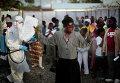 Женщину с выпиской из лечебного центра опрыскивают с целью дезинфекции от лихорадки Эбола, Монровия. 30 сентября 2014 год