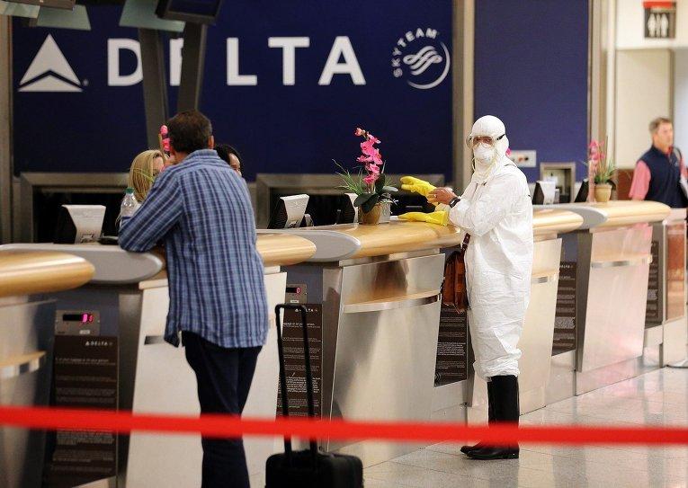 Доктор Джил Мобли, врач из Миссури, зарегистрировался и сел в самолет в защитном костюме. Международный аэропорт Атланты, 2 октября 2014