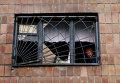 Женщина смотрит из окна своего дома, разрушенного после обстрела украинскими силовиками в Донецке