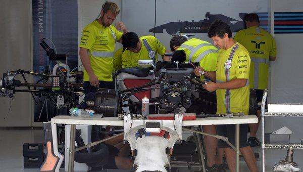 Механики готовят болид к соревнованиям в боксе перед началом российского этапа чемпионата мира по кольцевым автогонкам в классе Формула-1