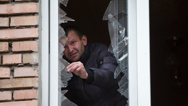 Мужчина убирает осколки от разбитого окна после обстрела Донецка 19 октября 2014