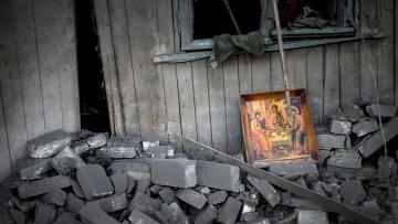 Икона во дворе дома после авиационного удара по станице Луганская