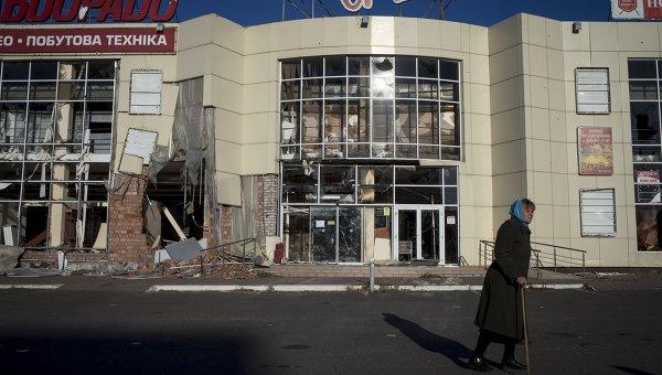 Женщина у разрушенного торгового центра в городе Луганске. Архивное фото