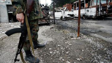 Вооруженный солдат на дороге в Донецке после обстрела