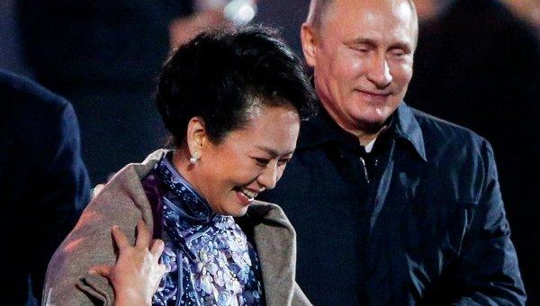 Президент России Владимир Путин накидывает пальто на плечи первой леди Китая  Пэн Лиюань